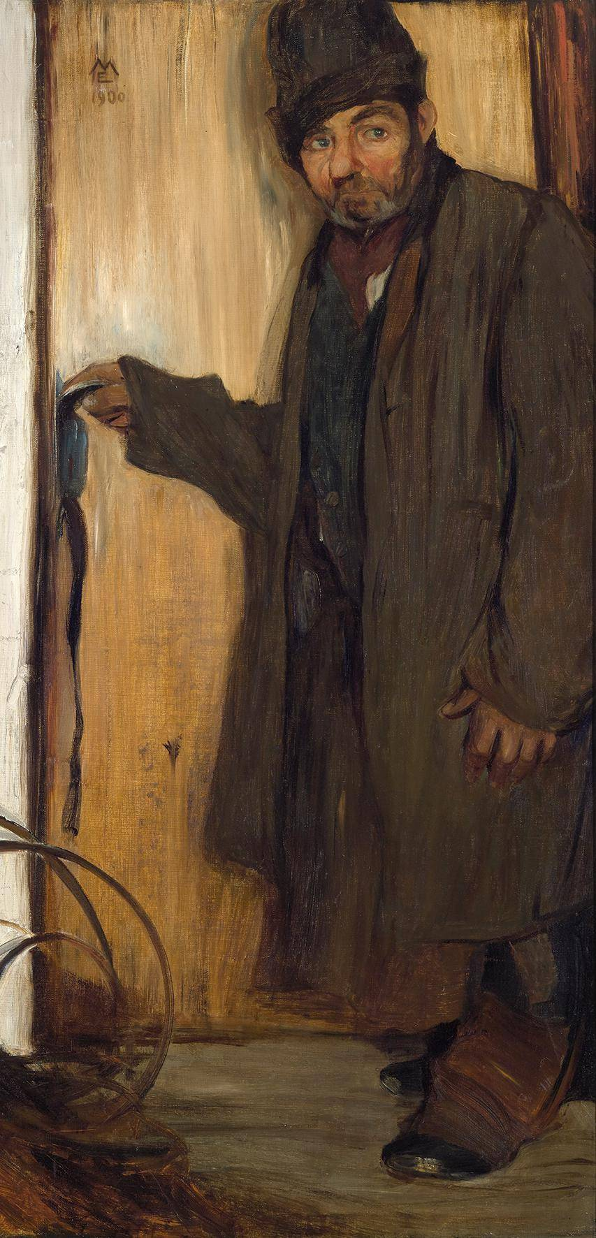 Man in a brown coat in front of a door